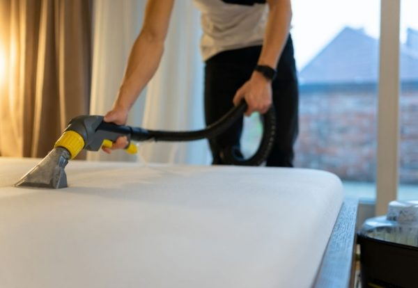 Mattress cleaning process. Man cleans bed from dirt and bacteria